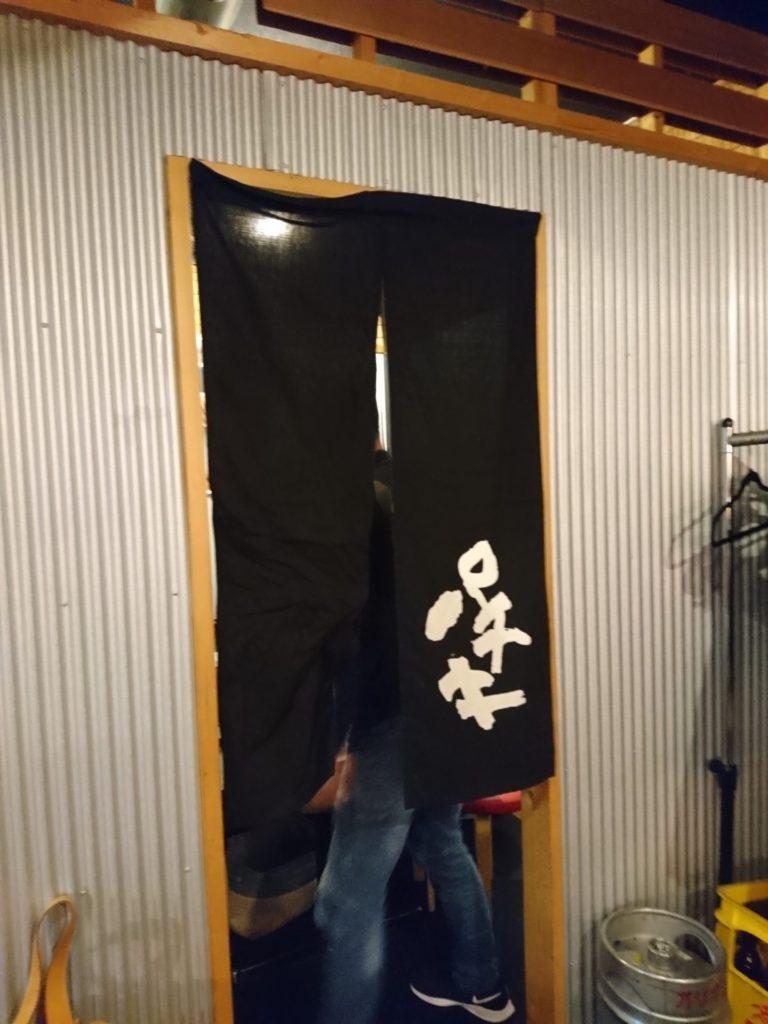 店内に掛けられた黒いのれんの画像
