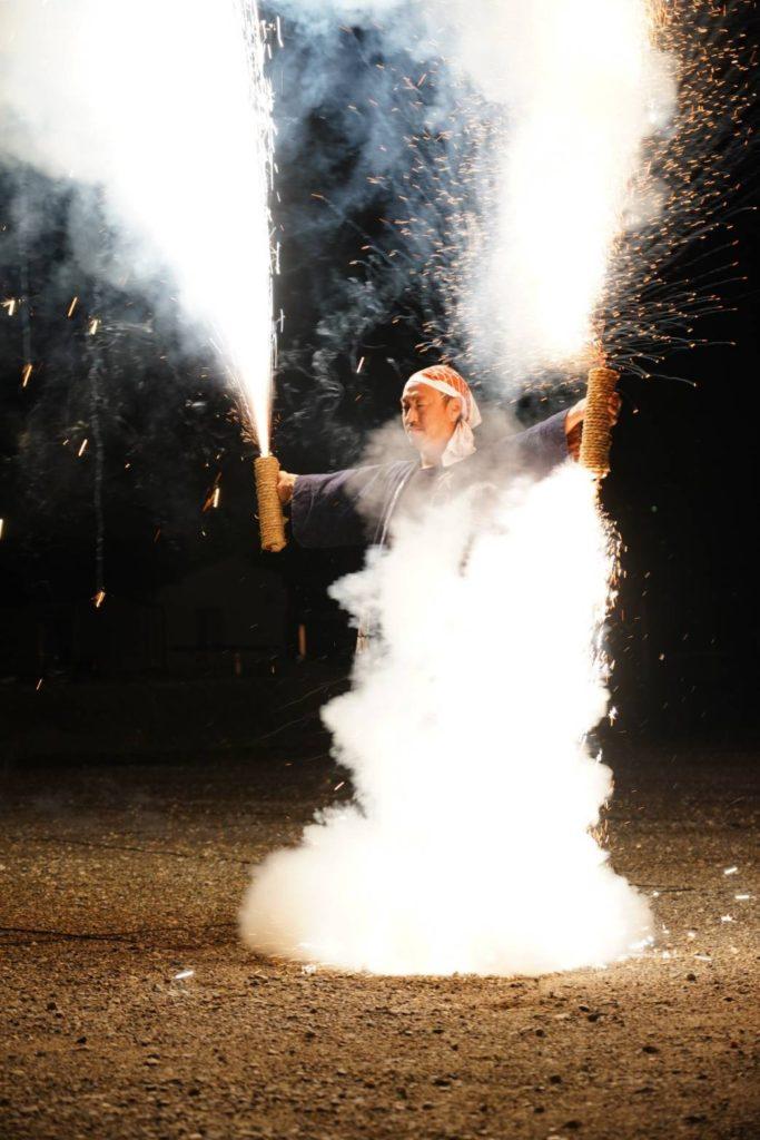 ハチマキをして手筒花火をあげている画像