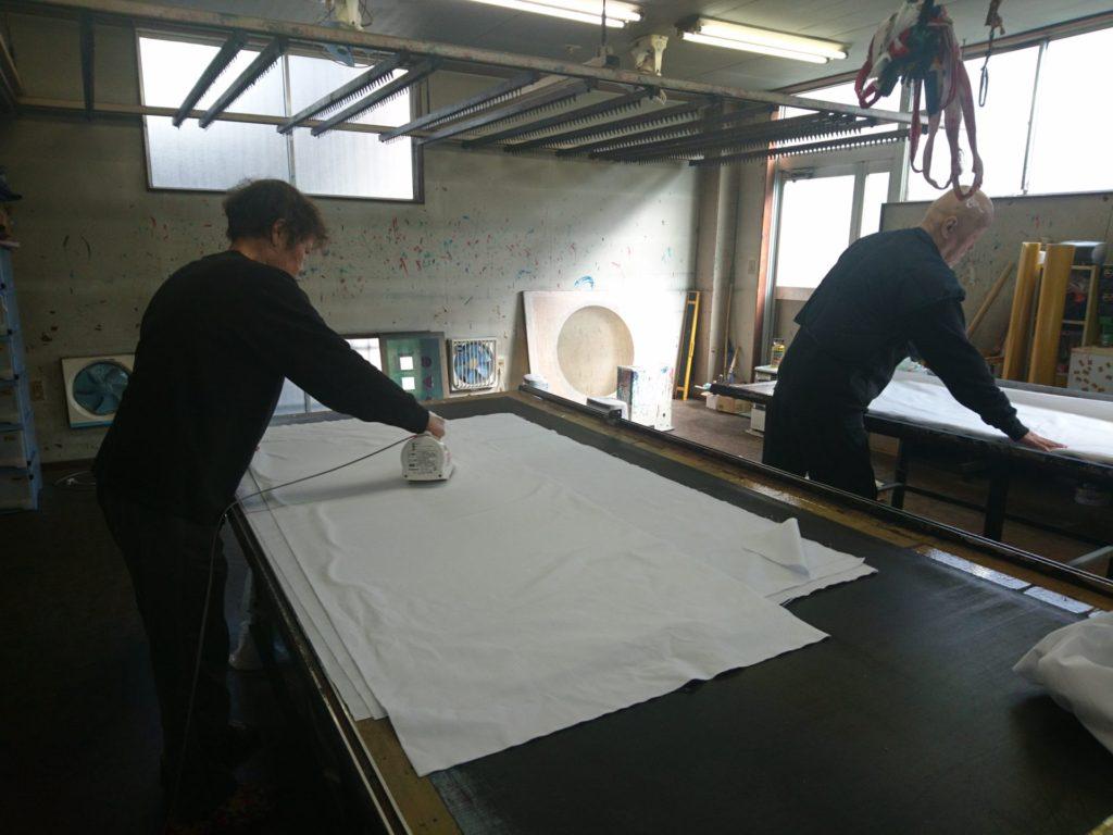 四巾天竺木綿生地にアイロンがけをしている画像。