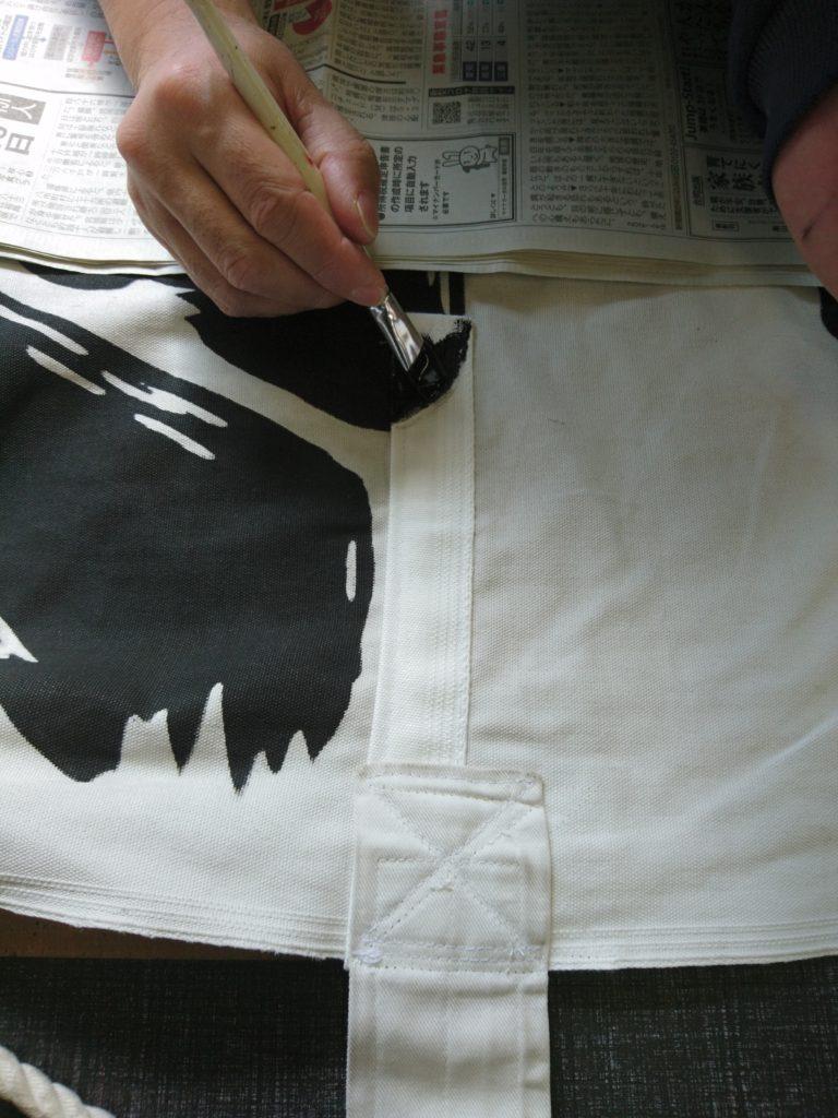 修理した幟を染め加工している作業の画像